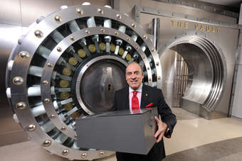 Coca-Cola Cos CEO, Muhtar Kent, holds the  secret formula in front of the entrance to a new permanent exhibit