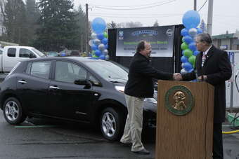 Washington state governor Jay Inslee (right) presents Steve Marsh with a special pin as Washingtonian of the Day in celebration of Marsh reaching 100,000 petrol-free miles in his 2011 Nissan Leaf. Marsh, a Kent resident, is the first known owner to drive 100,000 miles