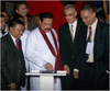 Sri Lanka's president Mahinda Rajapaksa using an iPad to launch a 3D video mapping technique at the Brandix stand at Expo 2012