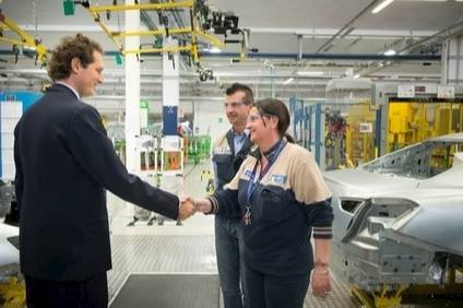 Hed like to shake hands on a deal. John Elkann meets workers at a Maserati plant