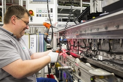 A worker fits cooling hoses to battery modules at Kamenz